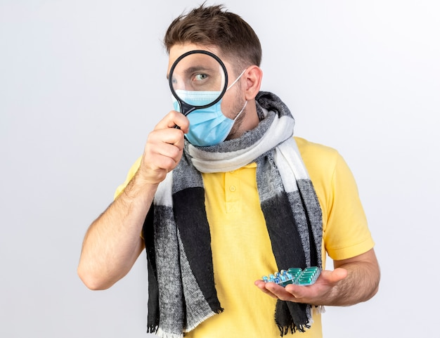 Zadowolony młody blond chory słowiański mężczyzna w masce medycznej i szaliku przez szkło powiększające i trzyma paczki pigułek medycznych na białej ścianie z miejscem na kopię