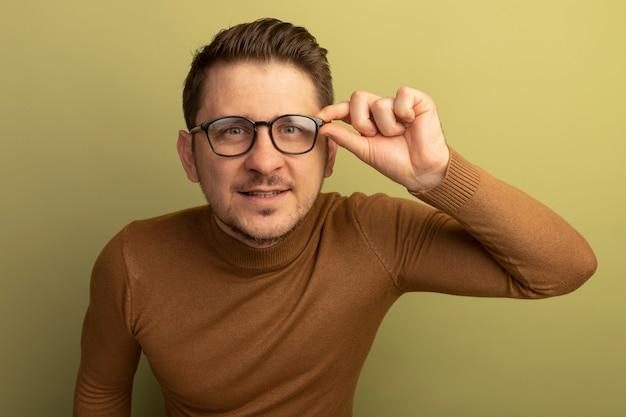 Zadowolony młody blond przystojny mężczyzna noszący i chwytający okulary patrząc odizolowany na oliwkowozielonej ścianie