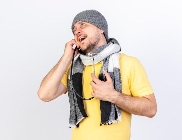 Zadowolony młody blondyn chory w czapce zimowej i szaliku trzyma stetoskop patrząc w górę na białym tle na białej ścianie
