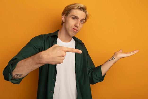 Zadowolony młody blondyn ubrany w zieloną koszulkę, udający, że trzyma i wskazuje na coś