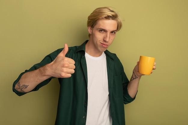 Zadowolony młody blondyn ubrany w zielony t-shirt, trzymając filiżankę herbaty i pokazując kciuk do góry