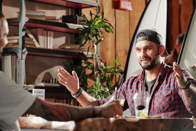 Zadowolony młody brodaty mężczyzna pokazuje rozmiar z rękami do przyjaciela, gdy omawiają surfowanie w letniej kawiarni