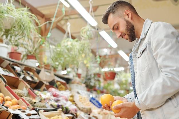 Zadowolony młody brodaty mężczyzna w dżinsowej kurtce stoi przy ladzie z jedzeniem i wybiera między dwoma pomarańczami