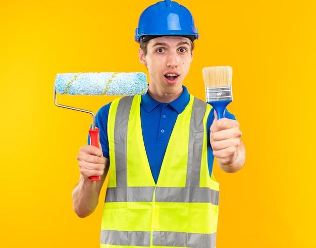 Zadowolony młody budowniczy mężczyzna w mundurze trzymający pędzel rolkowy z pędzlem