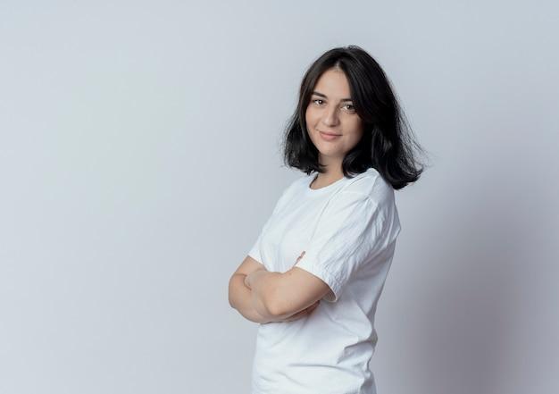 Zadowolony młody całkiem kaukaski dziewczyna stojąca z zamkniętą postawą w widoku profilu na białym tle na białym tle z miejsca na kopię