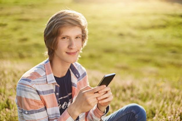 Zadowolony młody chłopak o ciemnych, wąskich oczach i stylowych włosach siedzi na łące, trzymając telefon komórkowy, sprawdzając pocztę elektroniczną lub czytając wiadomości, korzystając z bezpłatnego łącza internetowego podczas odpoczynku na pięknym zielonym polu