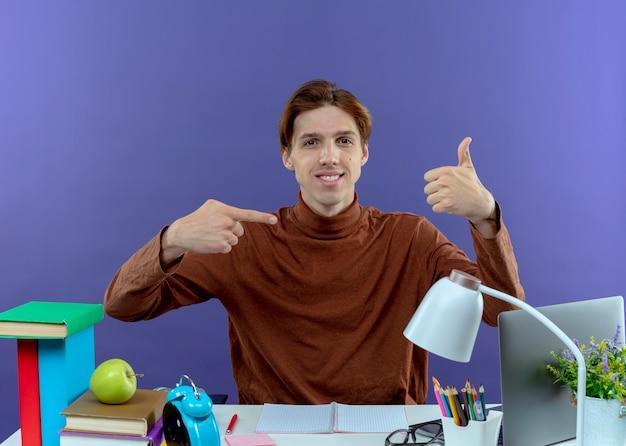 Zadowolony młody chłopak siedzi przy biurku z narzędziami szkolnymi, pokazując różne gesty na fioletowo