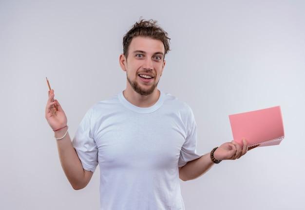 Zadowolony młody chłopak ubrany w białą koszulkę podnosząc ołówek i notatnik na ręce na na białym tle