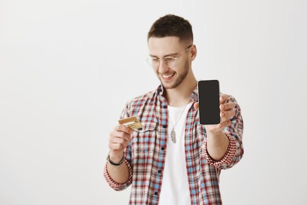 Zadowolony młody chłopak w okularach pozuje z jego telefonem i kartą