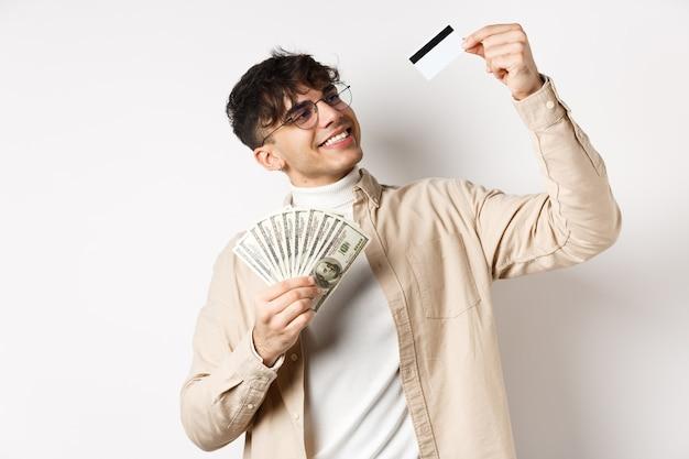 Zadowolony młody chłopak z pieniędzmi, zadowolony i uśmiechnięty do plastikowej karty kredytowej, wybiera płatności zbliżeniowe, stojąc na białej ścianie.