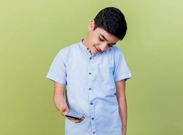 Zadowolony młody chłopiec kaukaski przechylając głowę na bok, trzymając i patrząc na telefon komórkowy na białym tle na oliwkowej ścianie z miejsca na kopię