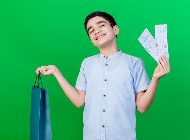 Zadowolony młody chłopiec kaukaski trzymając torbę na zakupy i bilety lotnicze na białym tle na zielonej ścianie