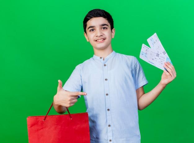 Zadowolony młody chłopiec kaukaski trzymając torbę na zakupy i bilety lotnicze, wskazując na bilety patrząc na kamery na białym tle na zielonym tle