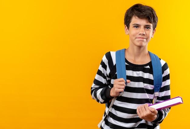 Zadowolony młody chłopiec w szkole w plecaku trzymającym książkę