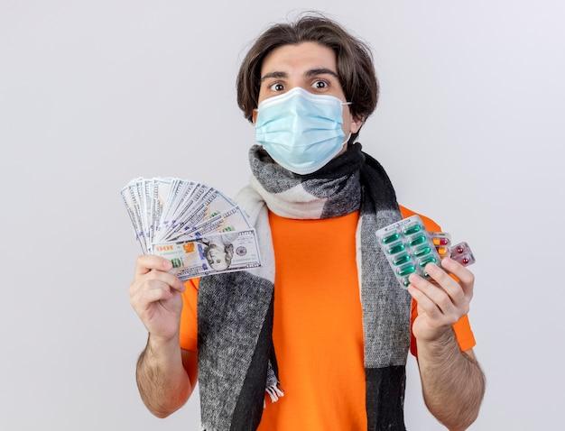 Zadowolony, młody chory człowiek ubrany w szalik i maskę medyczną, trzymając pieniądze z pigułki na białym tle