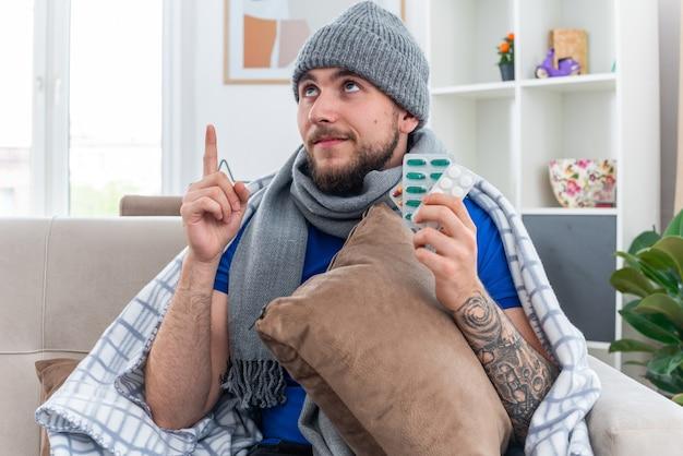 Zadowolony młody chory mężczyzna ubrany w szalik i zimową czapkę zawiniętą w koc, siedzący na kanapie w salonie, trzymający poduszkę, trzymający paczki pigułek, patrząc i wskazując w górę