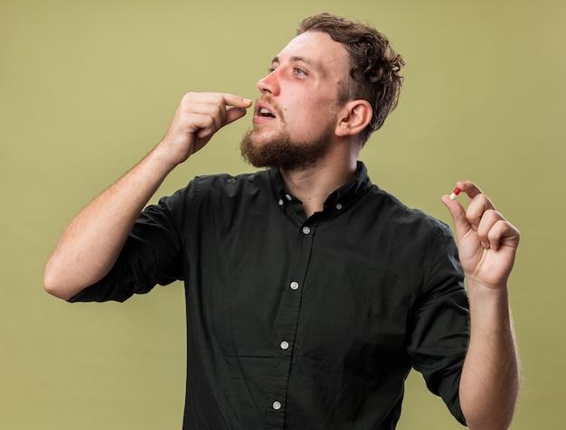 Zadowolony młody chory słowiański mężczyzna biorący pigułki z lekami, patrząc na bok