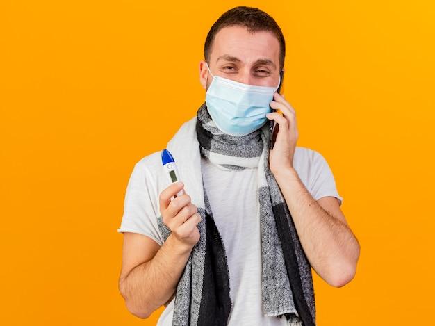 Zadowolony młody chory w czapce zimowej i masce medycznej mówi przez telefon i trzyma termometr na białym tle na żółtym tle