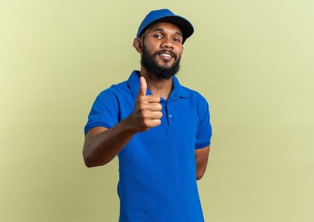 Zadowolony Młody Człowiek Dostawy Kciukiem Na Białym Tle Na Oliwkowozielonej ścianie Z Miejscem Na Kopię Darmowe Zdjęcia