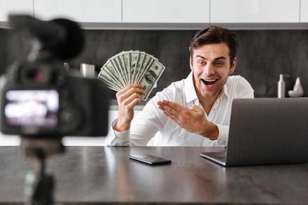 Zadowolony młody człowiek filmujący swój odcinek blogu wideo