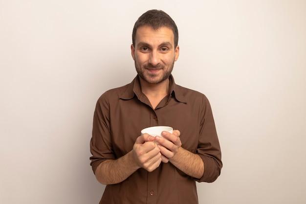 Zadowolony młody człowiek kaukaski trzymając kubek herbaty patrząc na kamery na białym tle na białym tle z miejsca na kopię