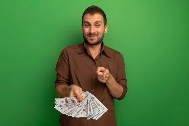 Zadowolony młody człowiek kaukaski trzymając pieniądze, patrząc i wskazując na aparat na białym tle na zielonym tle z miejsca na kopię