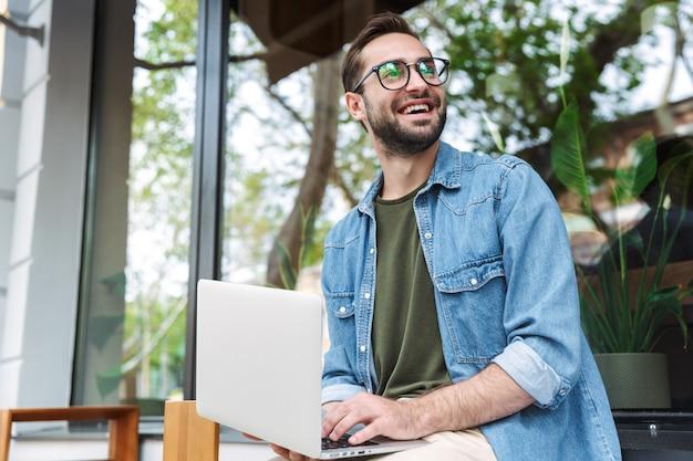 Zadowolony młody człowiek noszący okulary, piszący na laptopie podczas pracy w miejskiej kawiarni na świeżym powietrzu