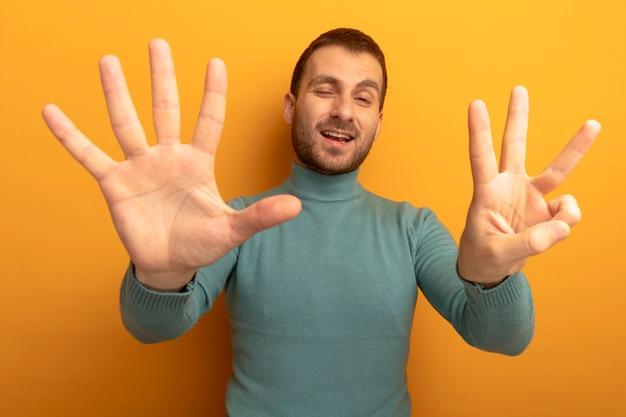 Zadowolony młody człowiek patrząc z przodu pokazuje osiem z mrugającymi rękami na białym tle na pomarańczowej ścianie