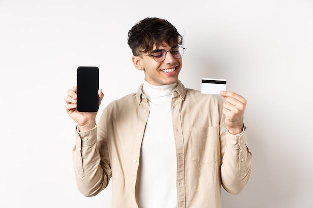 Zadowolony młody człowiek patrząc zadowolony z karty kredytowej, pokazując pusty ekran smartfona, stojąc na białej ścianie.