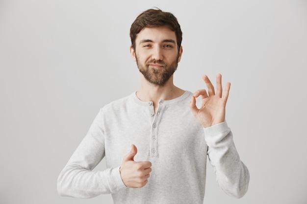 Zadowolony młody człowiek pokazuje kciuki do góry i znak w porządku