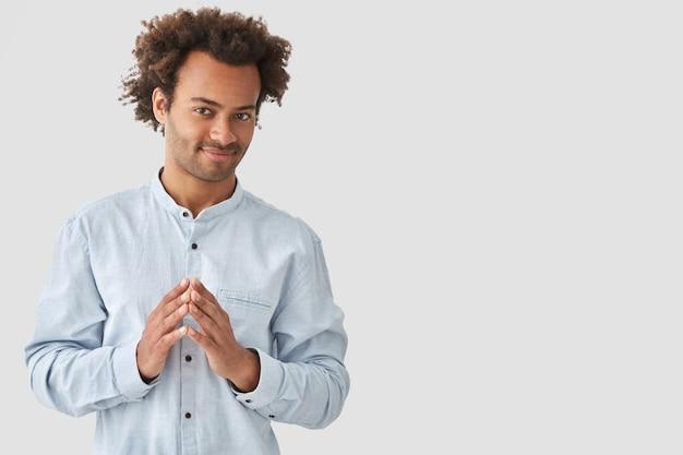 Zadowolony młody człowiek rasy mieszanej trzyma się za ręce, ma intrygujący wyraz i zamiar zrobienia czegoś, zamierza podzielić się swoimi planami z przyjacielem, odizolowany na białej pustej ścianie