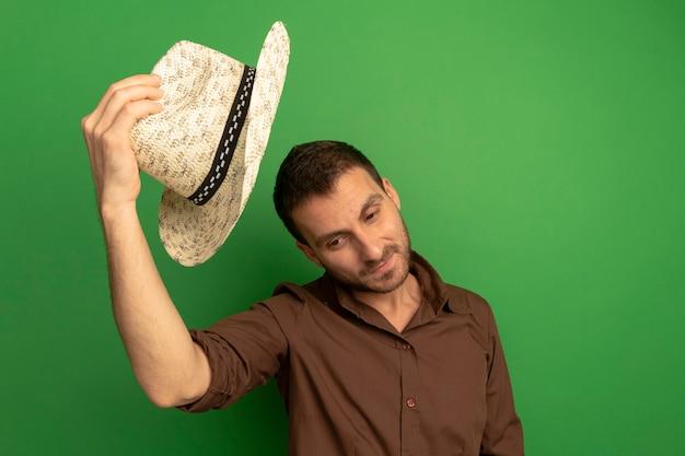 Zadowolony młody człowiek trzyma kapelusz plażowy nad głową, patrząc w dół na białym tle na zielonej ścianie