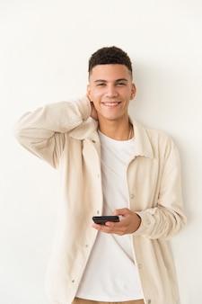 Zadowolony młody człowiek trzyma telefon komórkowego
