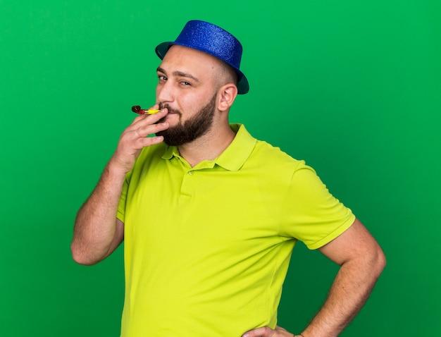 Zadowolony młody człowiek ubrany w niebieski kapelusz imprezowy dmuchający gwizdek kładący rękę na biodrze odizolowany na zielonej ścianie