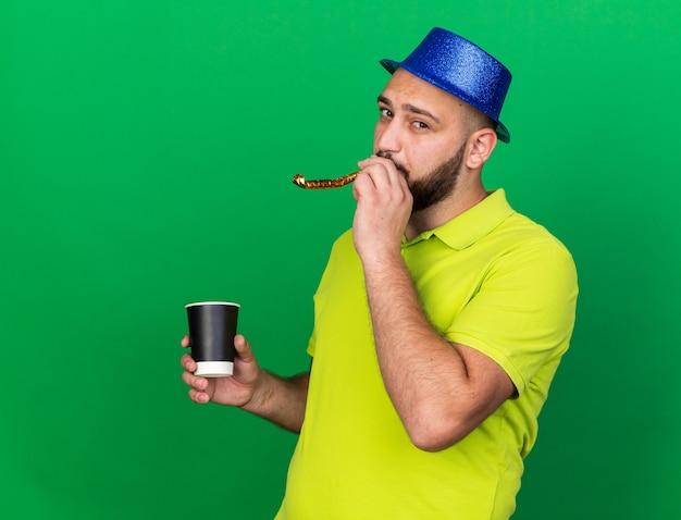 Zadowolony młody człowiek ubrany w niebieski kapelusz imprezowy dmuchający gwizdek trzymający filiżankę kawy odizolowaną na zielonej ścianie