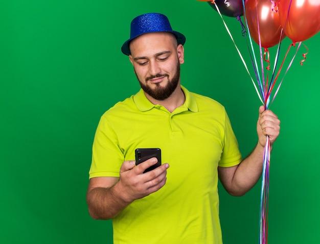 Zadowolony młody człowiek ubrany w niebieski kapelusz imprezowy, trzymający balony, trzymający i patrzący na telefon