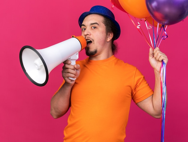 Zadowolony młody człowiek w imprezowym kapeluszu, trzymający balony, mówi przez głośnik