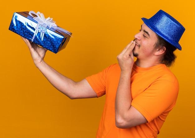 Zadowolony młody człowiek w imprezowym kapeluszu, trzymający i patrzący na pudełko pokazujące pyszny gest