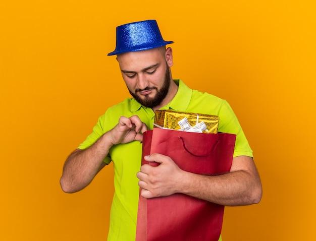 Zadowolony młody człowiek w kapeluszu imprezowym, trzymający i patrzący na torbę na prezent