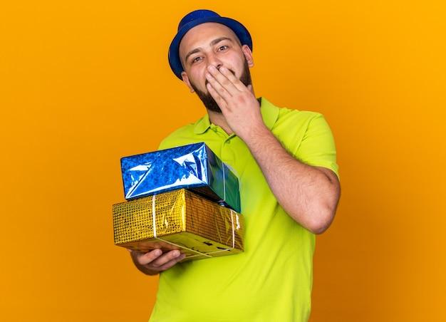 Zadowolony młody człowiek w kapeluszu imprezowym, trzymający pudełka z prezentami, zakrywające usta ręką odizolowaną na pomarańczowej ścianie