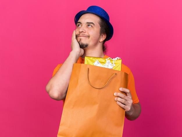 Zadowolony młody człowiek w kapeluszu imprezowym, trzymający torbę z prezentami, kładąc rękę na policzku na różowej ścianie