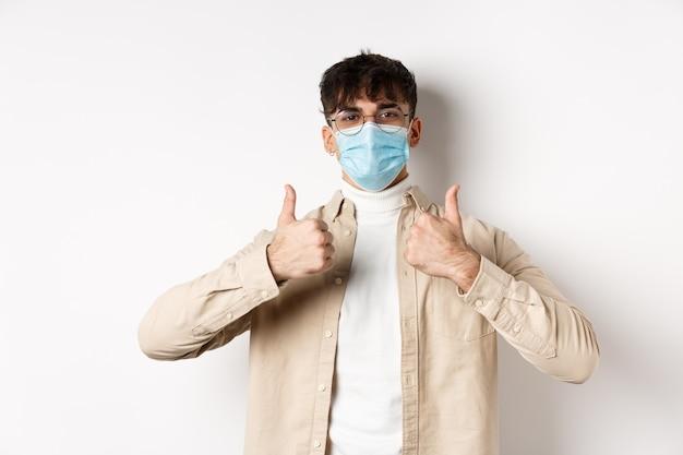 Zadowolony młody człowiek w masce z kciukami do góry, stosując środki zapobiegawcze przed rozprzestrzenianiem się covid-19. koncepcja koronawirusa, kwarantanny i dystansu społecznego.