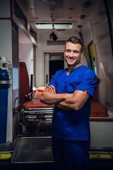 Zadowolony młody człowiek w mundurze medycznym, w tle karetka pogotowia.