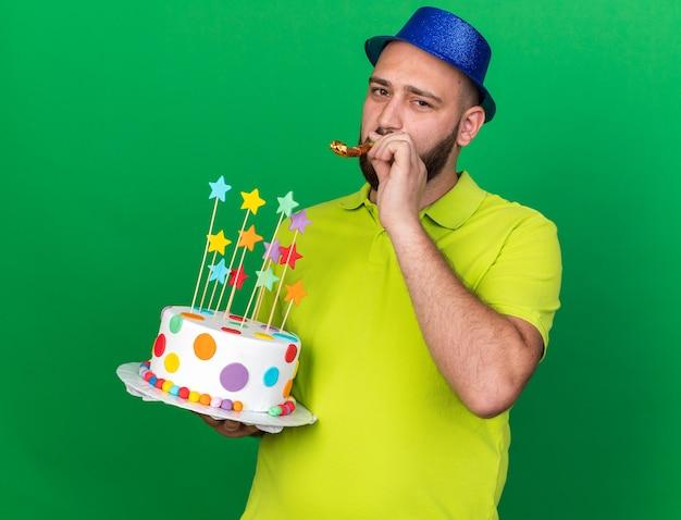 Zadowolony młody człowiek w niebieskiej imprezowej czapce, trzymający gwizdek na tort