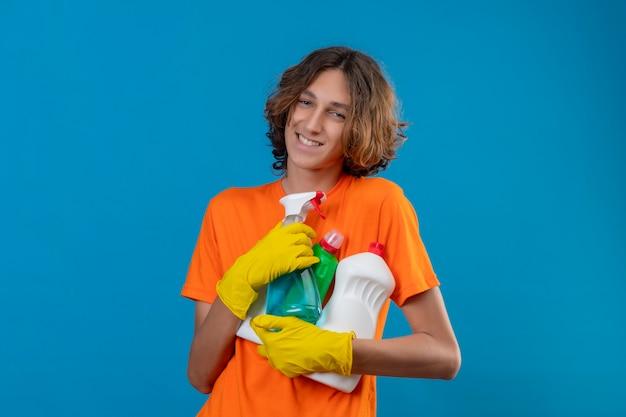 Zadowolony młody człowiek w pomarańczowej koszulce w gumowych rękawiczkach trzymający narzędzia do czyszczenia patrząc na kamerę z radosną twarzą uśmiechniętą wesoło stojąc na niebieskim tle