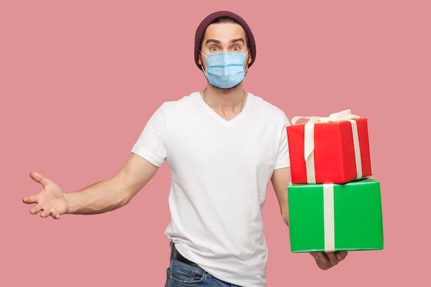 Zadowolony młody człowiek z chirurgiczną maską medyczną w białej koszuli i swobodnym kapeluszu stojącym, trzymający dwa obecne pudełko z podniesionymi rękami, patrzący w kamerę. wewnątrz, na białym tle, studio strzał, różowe tło