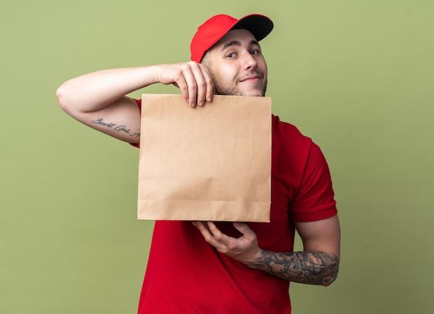 Zadowolony młody dostawca w mundurze z czapką trzymającą papierową torbę z jedzeniem
