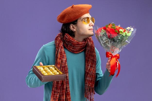 Zadowolony młody facet na walentynki w kapeluszu z szalikiem i okularami, trzymając pudełko cukierków wąchających bukiet w ręku na białym tle na niebieskim tle