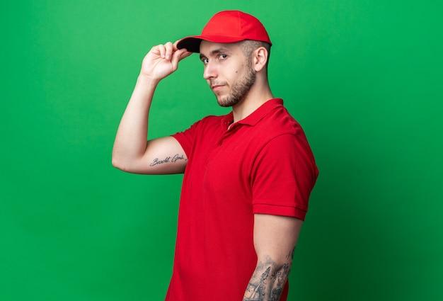 Zadowolony młody facet od dostawy ubrany w mundur z czapką trzymającą czapkę