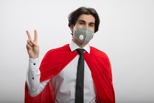 Zadowolony młody facet superbohatera patrząc na kamery na sobie krawat i maskę medyczną pokazujący gest pokoju na białym tle